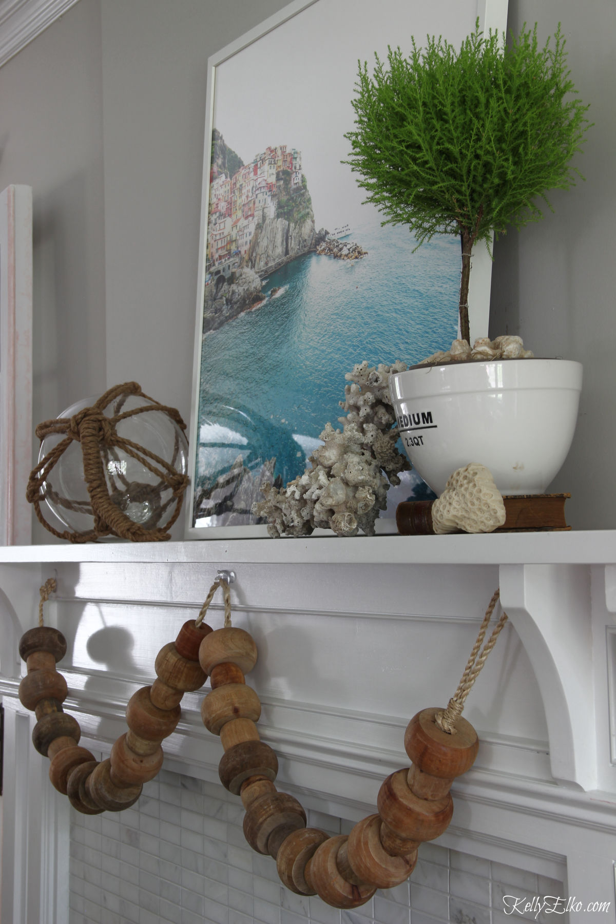 Love the big chunky wood beads on this coastal summer mantel kellyelko.com #summer #mantel #summermantel #coastal #coastaldecor #topiary