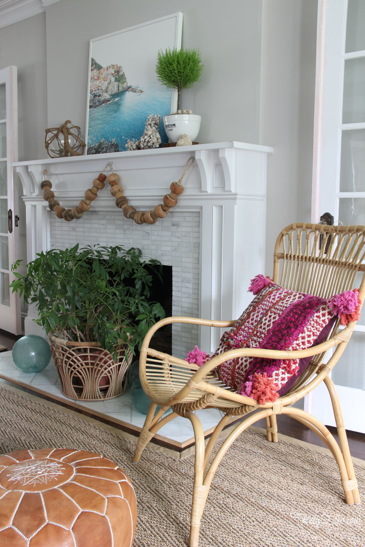 Love this coastal summer mantel and the big chunky wood bead garland kellyelko.com #coastal #mantel #summerdecor #coastaldecor #summermantel #manteldecor #houseplants #rattan #boho #bohodecor #eclecticdecor
