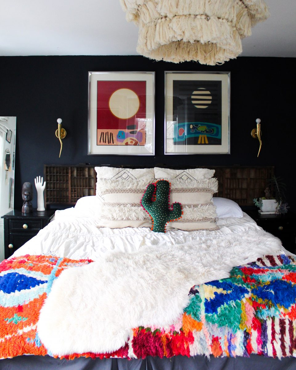 Love the dark black walls in this boho bedroom and the colorful bedding and art kellyelko.com #bedrooms #bedroomdecor #bohobedroom #bohodecor #vintagedecor #macrame #vintagemodern