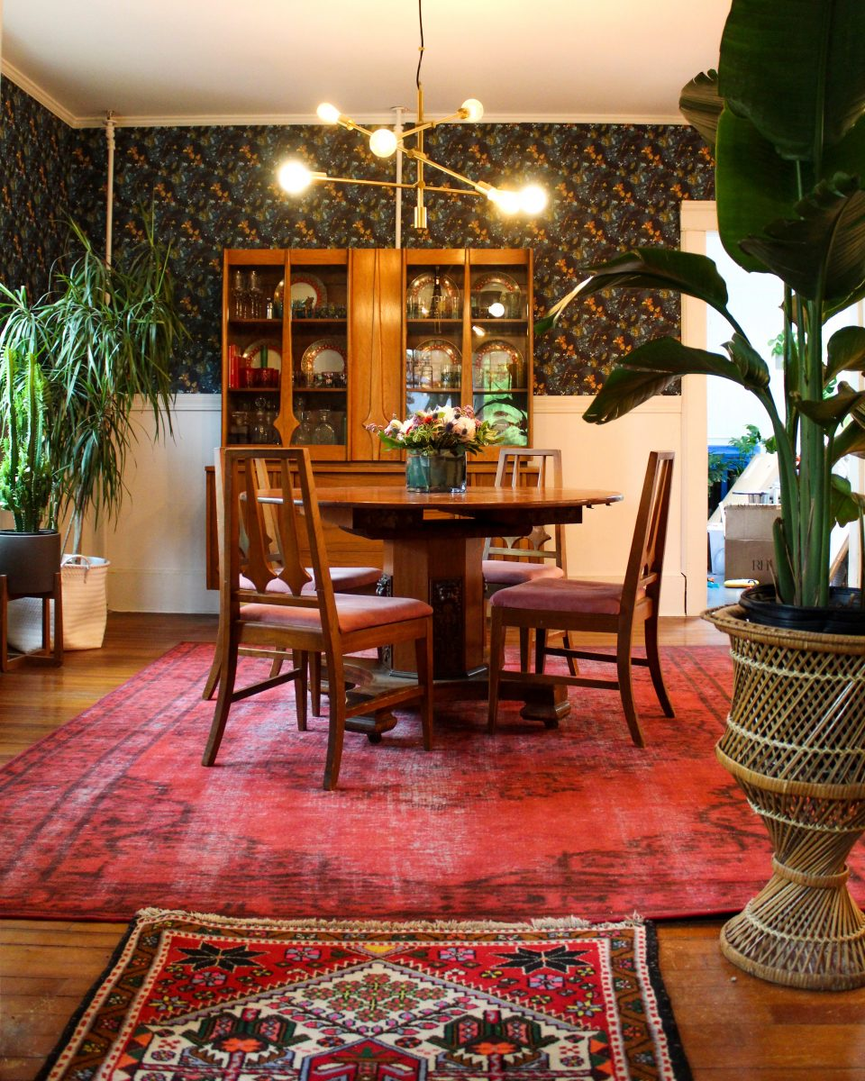 Colorful boho dining room filled with thrift store vintage finds and colorful antique rugs kellyelko.com #diningroom #diningroomdecor #vintagedecor #lighting #vintagemodern #plantlady #vintagerugs #midcenturymodern