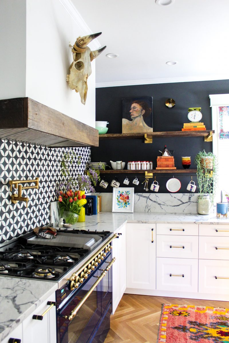 Eclectic Home Tour - love this white kitchen with black walls, open shelves and blue stove kellyelko.com #kitchen #homedecor #kitchens #openshelves #whitekitchen #hometour #bohodecor #eclectic #vintagedecor
