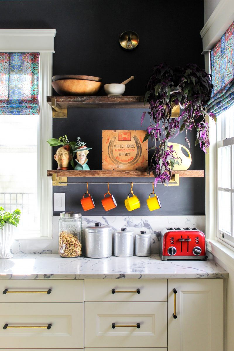 Love the rustic wood shelves against the black painted walls in this white kitchen kellyelko.com #bohodecor #vintagedecor #kitchendecor #kitchens #openshelves