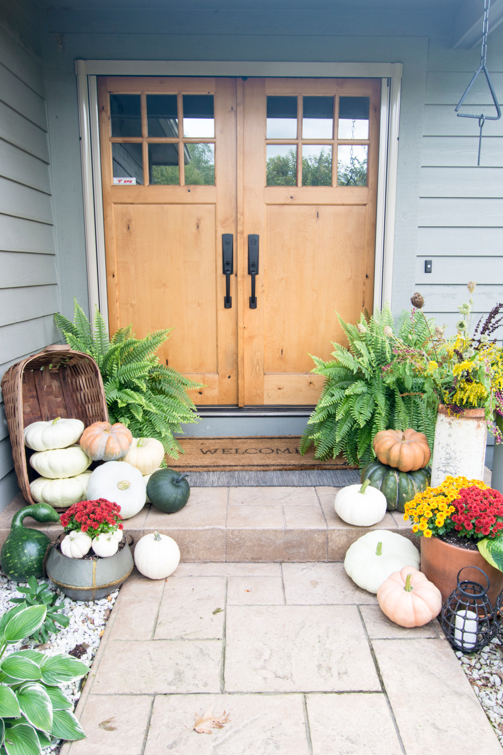 10 Beautiful Fall Porches - love the pumpkins spilling out of the basket kellyelko.com #fall #fallporch #falldecor #falldecorating #pumpkins #curbappeal #autummdecor #autummporch