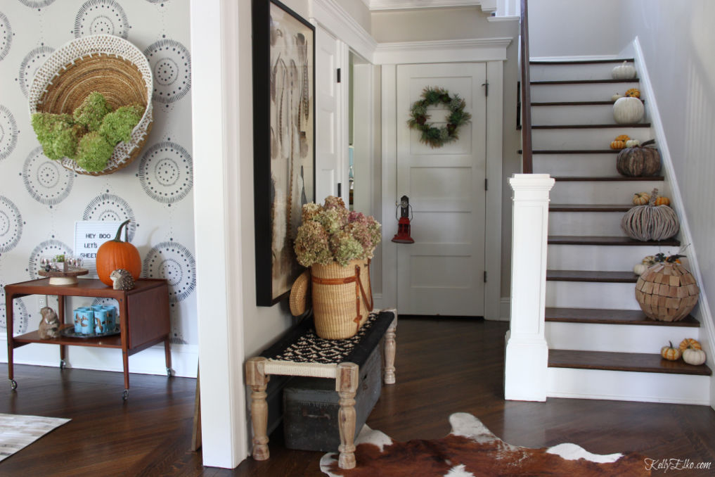 Fall home tour - love the staircase of neutral pumpkins and the huge wall basket filled with hydrangeas kellyelko.com #foyer #foyerdecor #falldecor #falldecorating #basket #bohodecor #vintagedecor #pumpkins #pumpkindecor #entrydecor
