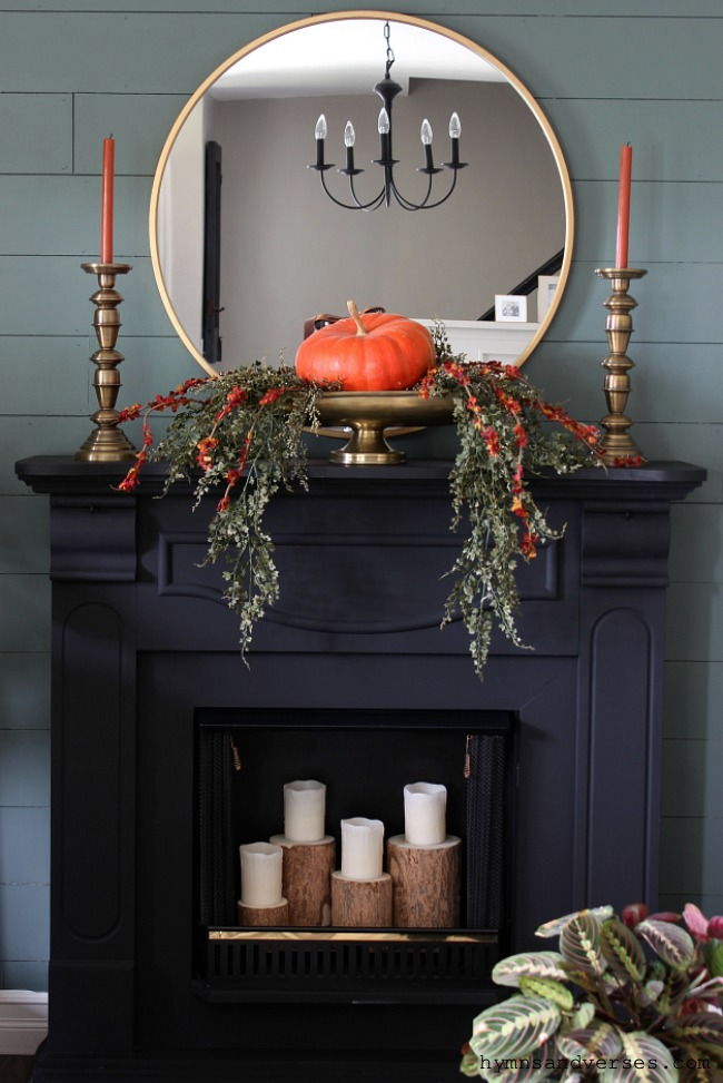 12 Creative Fall Mantels - love this moody black mantel with single pumpkin in an urn kellyelko.com #falldecor #fallmantel #mantel #manteldecor #pumpkins #blackpaint #shiplap #fireplace