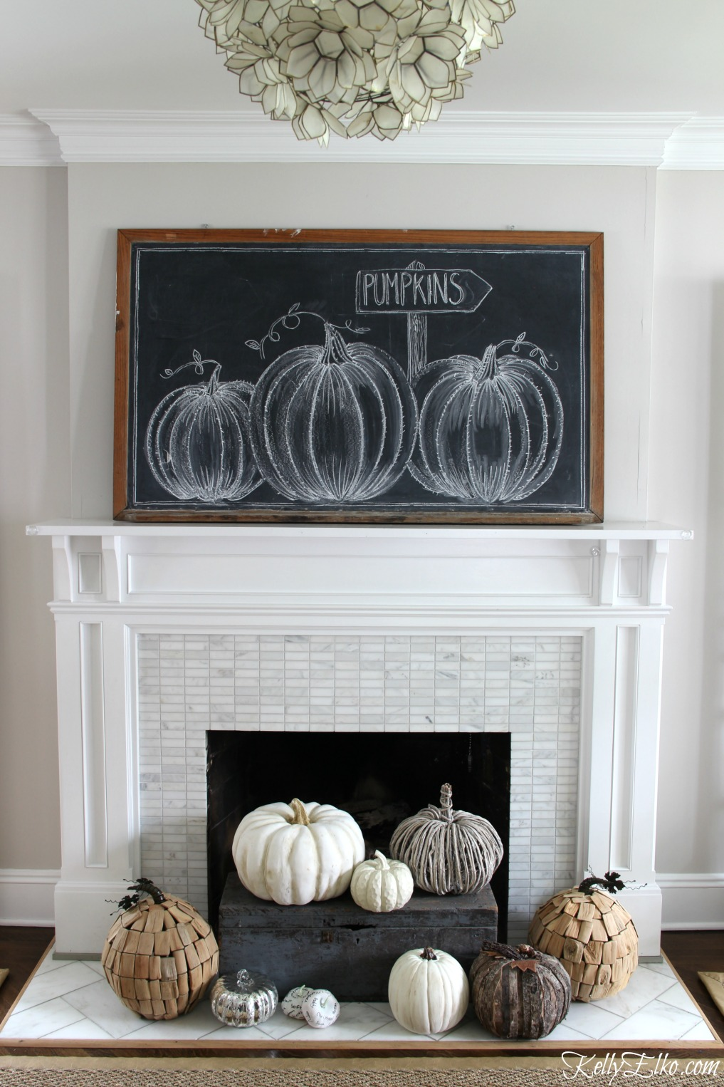 Love this farmhouse fall mantel with giant pumpkin chalkboard art and neutral pumpkins kellyelko.com
