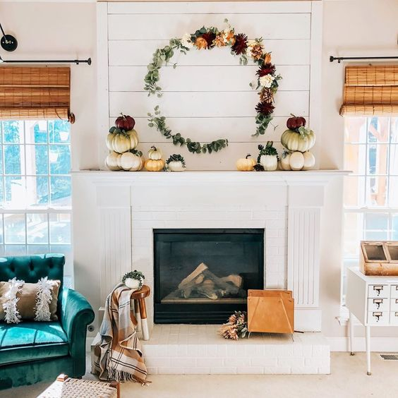 12 Creative Fall Mantels - love this DIY floral wreath and stacked pumpkins kellyelko.com #fall #falldecor #fallmantel #diywreath #wreaths #diycrafts #neutraldecor #farmhousedecor #shiplap #manteldecor