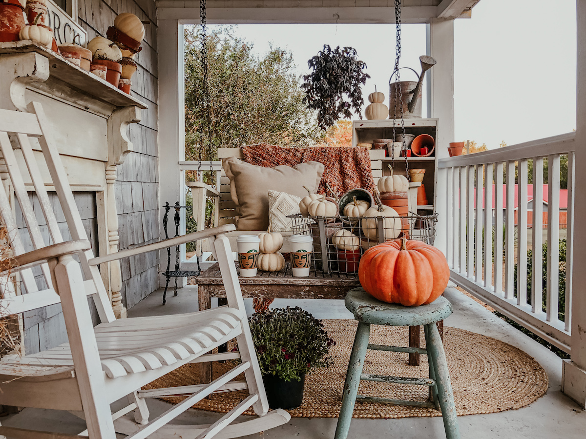 Farmhouse front porch decorated for fall - love the chippy wood mantel and piles of pumpkins kellyelko.com #fall #falldecor #fallporch #farmhousedecor #farmhouseporch #porchdecor #frontporch #farmhousestyle