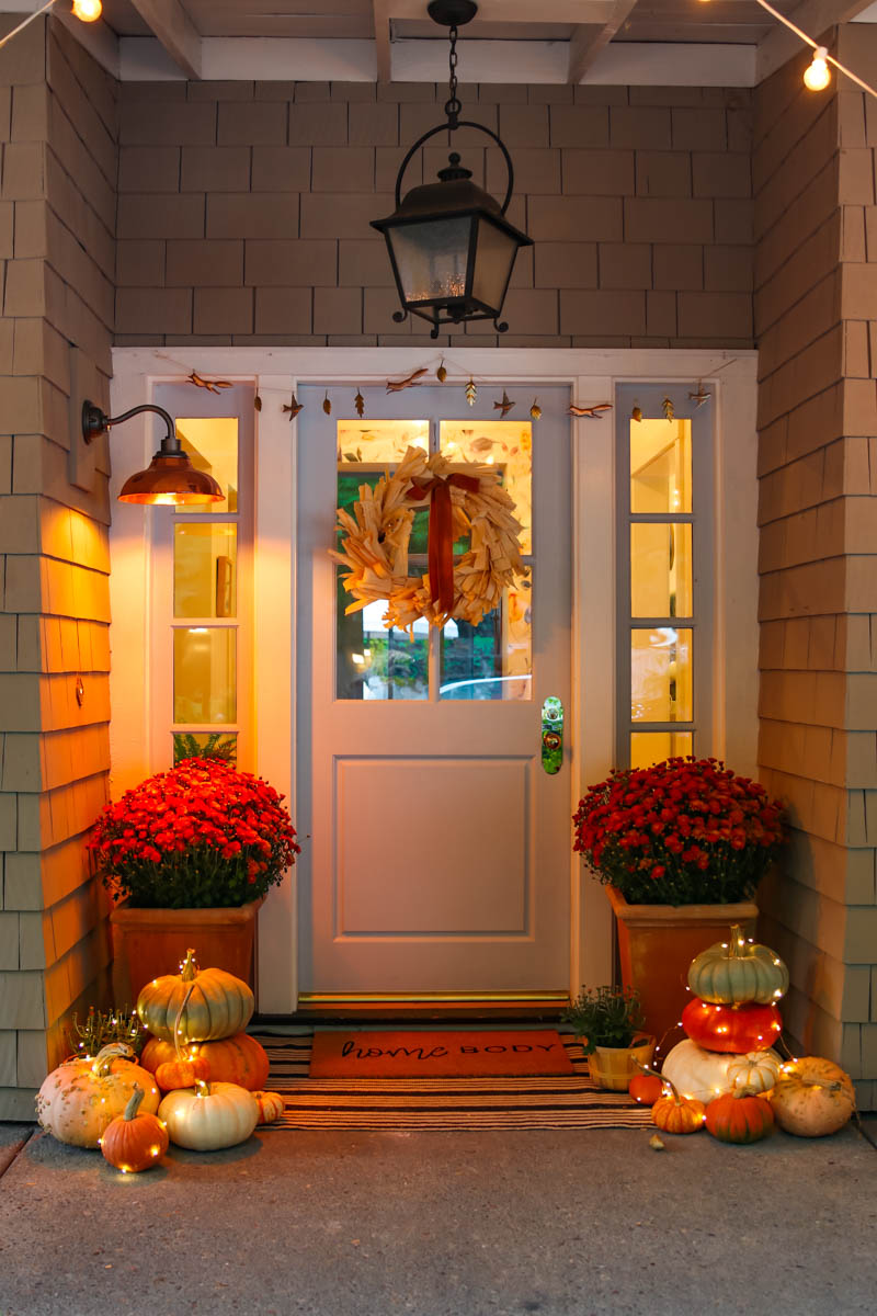 10 Beautiful Fall Porches - love the fairy lights wrapped around the pumpkins kellyelko.com #fall #fallporch #falldecor #falldecorating #mums #pumpkins #fairylights #porch #frontporch #curbappeal #autummdecor #autummporch