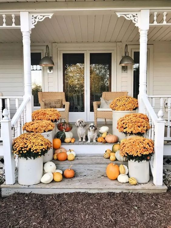 10 Beautiful Fall Porches - love the vintage crocks used as planters kellyelko.com #fall #fallporch #falldecor #falldecorating #mums #pumpkins #vintagefall #vintagedecor #farmhousedecor #porch #frontporch #curbappeal #autummdecor #autummporch