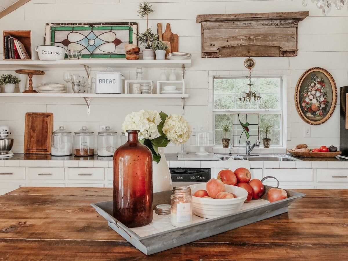 Love this farmhouse kitchen with shiplap walls and open shelves for vintage displays kellyelko.com #kitchendecor #vintagedecor #whitekitchen #farmhousedecor #farmhousekitchen #eclecticdecor #shiplapkitchen #openshelves