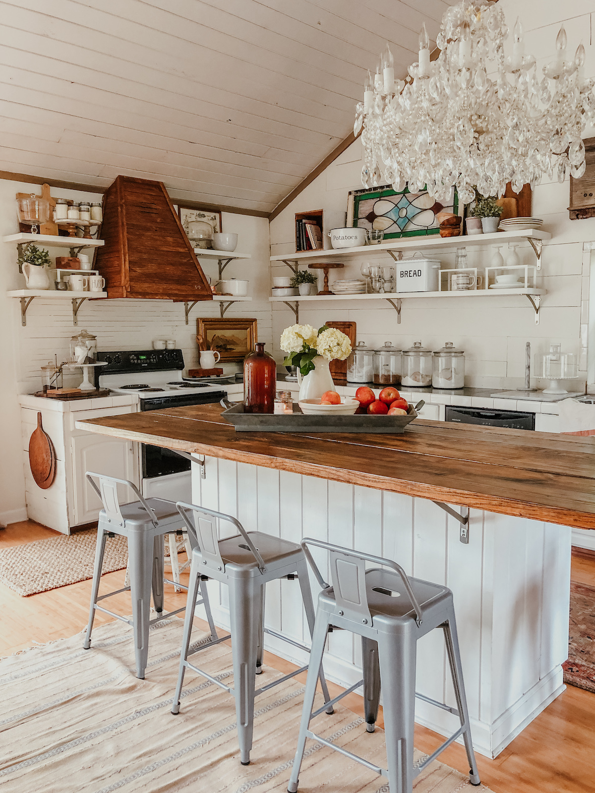 Beautiful farmhouse kitchen with shiplap, open shelves, crystal chandelier and DIY wood range hood kellyelko.com #farmhousedecor #farmhousekitchen #falldecor #kitchen #kitchendecor #whitekitchen #shiplapkitchen #vintagedecor
