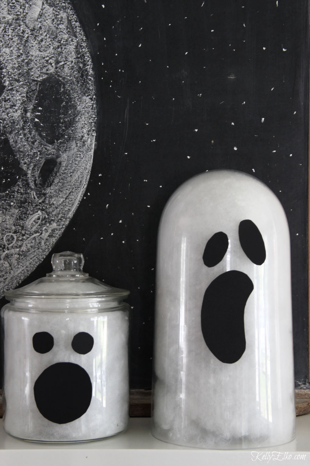 See how to make these cute glass jar ghosts for Halloween kellyelko.com #ghosts #halloweendecor #halloweendecorations #diyhalloween #halloweencrafts #halloweenmantel