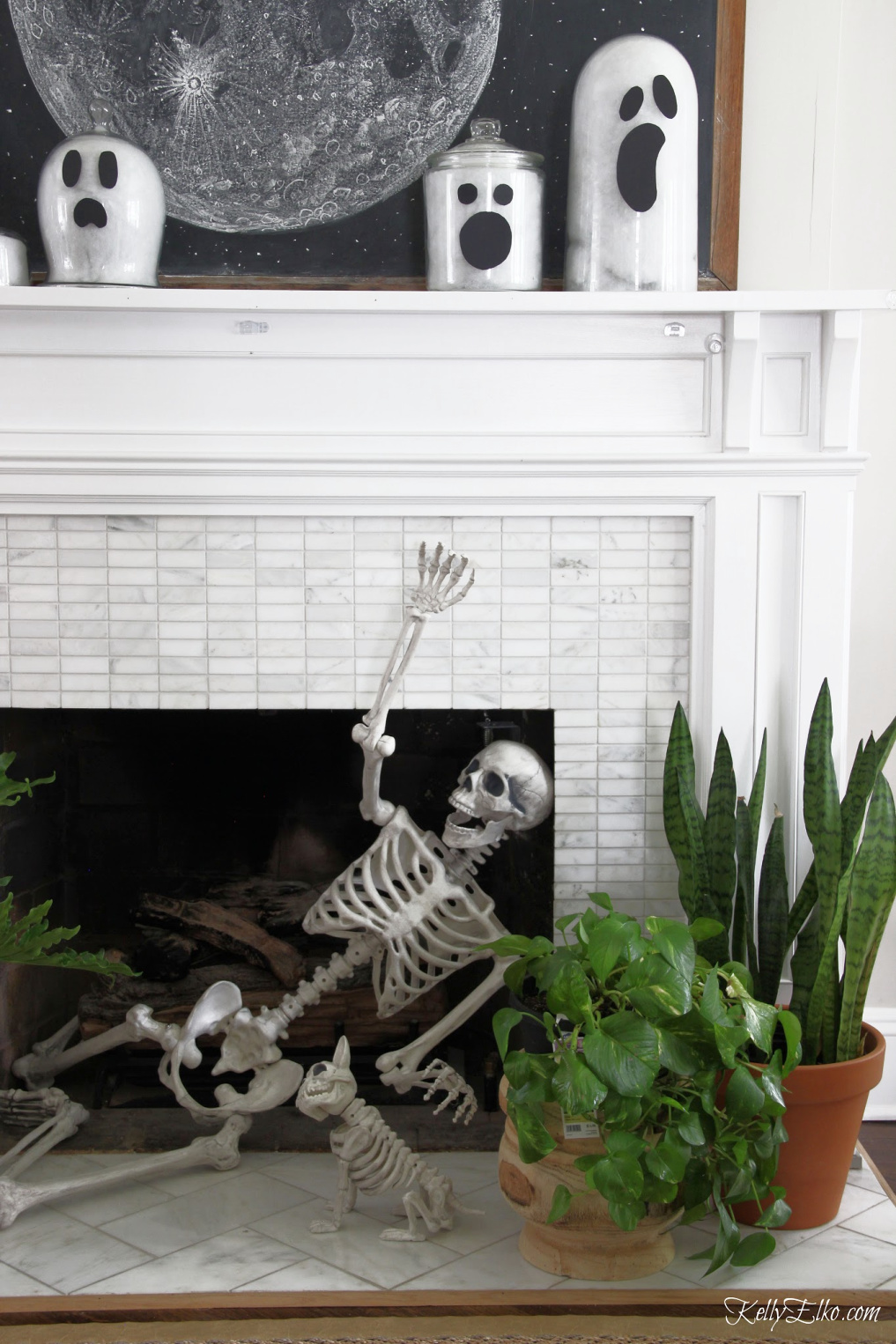 Love this Halloween mantel with the skeleton in the fireplace and she shows how to make glass jar ghosts! - kellyelko.com #halloween #halloweencrafts #halloweendecor #halloweendecorations #diyhalloween #diyhalloweendecorations #ghosts #skeleton #halloweenhouse #halloweenmantel #vintagehalloween