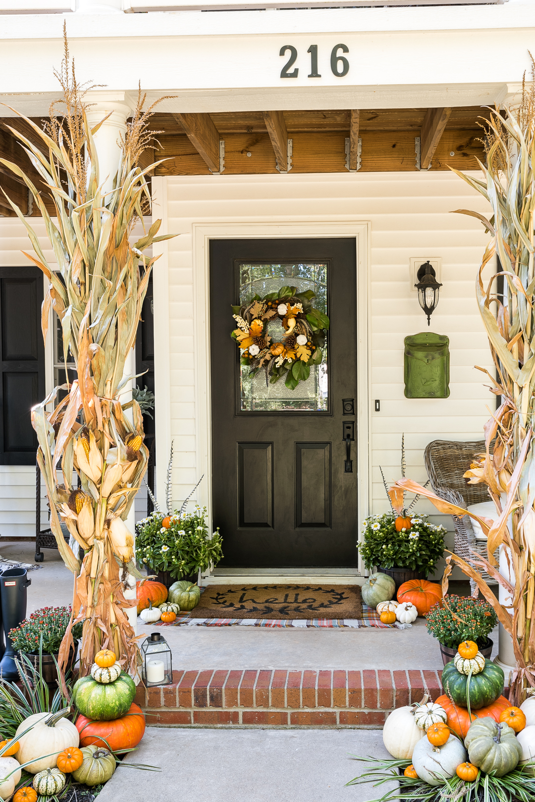 10 Beautiful Fall Porches - love the corn stalks and feathers in the planters kellyelko.com #fall #fallporch #falldecor #falldecorating #mums #pumpkins #fairylights #porch #frontporch #curbappeal #autummdecor #autummporch