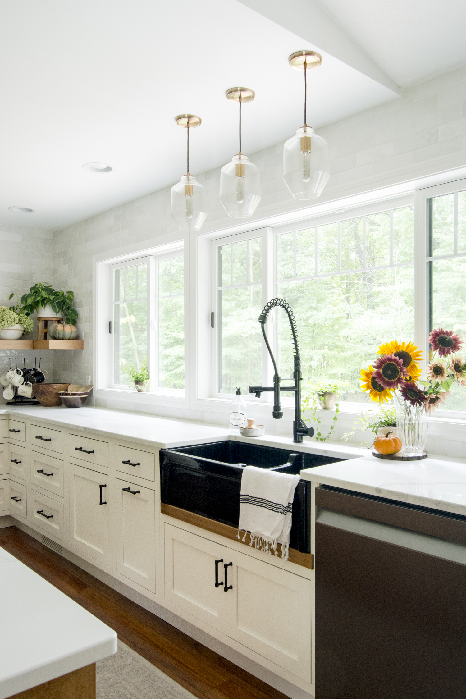 Love the black farmhouse sink and trip of glass pendant lights kellyelko.com #kitchen #kitchenlighting #lighting #farmhousesink #farmhousekitchen #farmhousedecor #whitekitchen #interiordesign