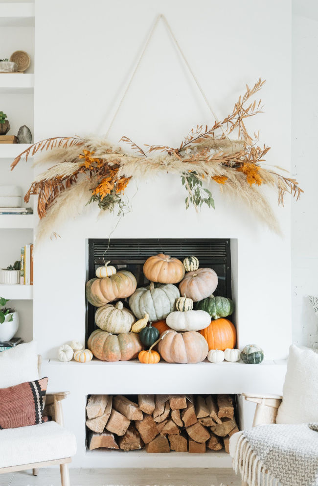 12 Creative Fall Mantels - this huge DIY pampas grass and wheat wall hanging is beautiful kellyelko.com #fall #falldecor #fallcrafts #diyideas #pumpkins #fallmantel #mantels #bohodecor