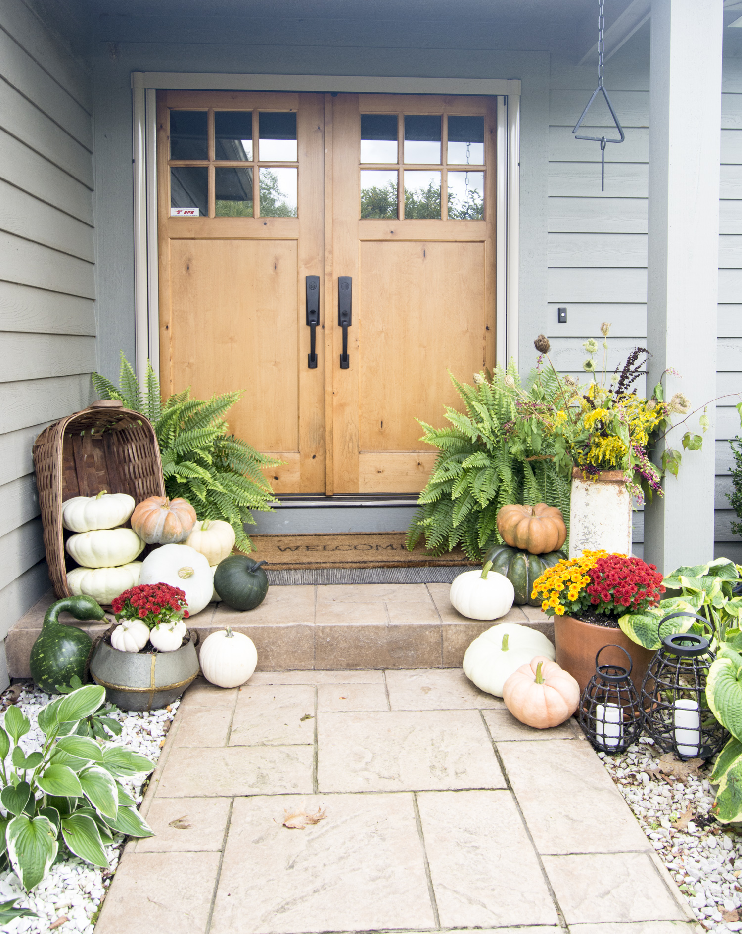 Love the wood double front doors and the pile of pumpkins spilling out of baskets on this fall front porch kellyelko.com #frontporch #porchdecor #pumpkins #falldecor #fallporch