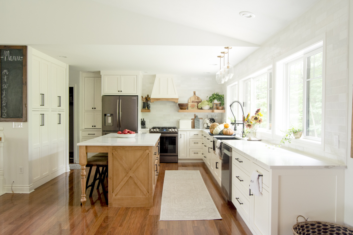 Beautifully renovated kitchen with white cabinets, huge windows and natural wood island kellyelko.com #kitchen #farmhousekitchen #kitchenreno #kitchendecor #kitchendesign #kitchenisland