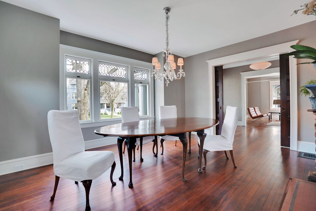 This old house has beautiful diamond paned windows and hardwood floors kellyelko.com #diningroom #diningroomdecor #oldhouse #oldhome #interiordecor #interiordesign #graypaint #slipcoverchairs #diningroomfurniture #vintagemodern