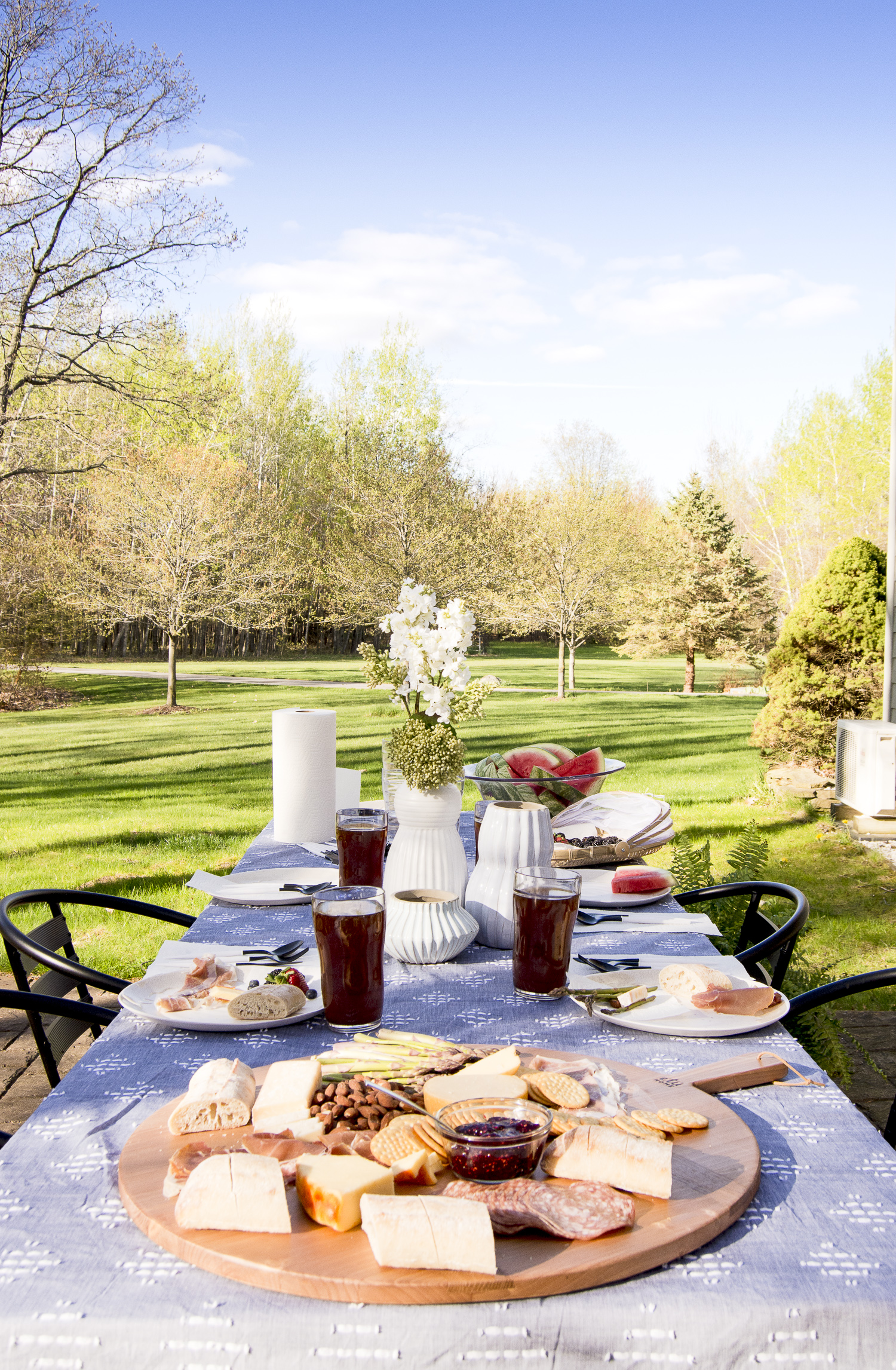 Beautiful table with charcuterie board kellyelko.com #charcuterie #outdoordining #outdoordecor #tablesetting #outdoors #backyarddecor