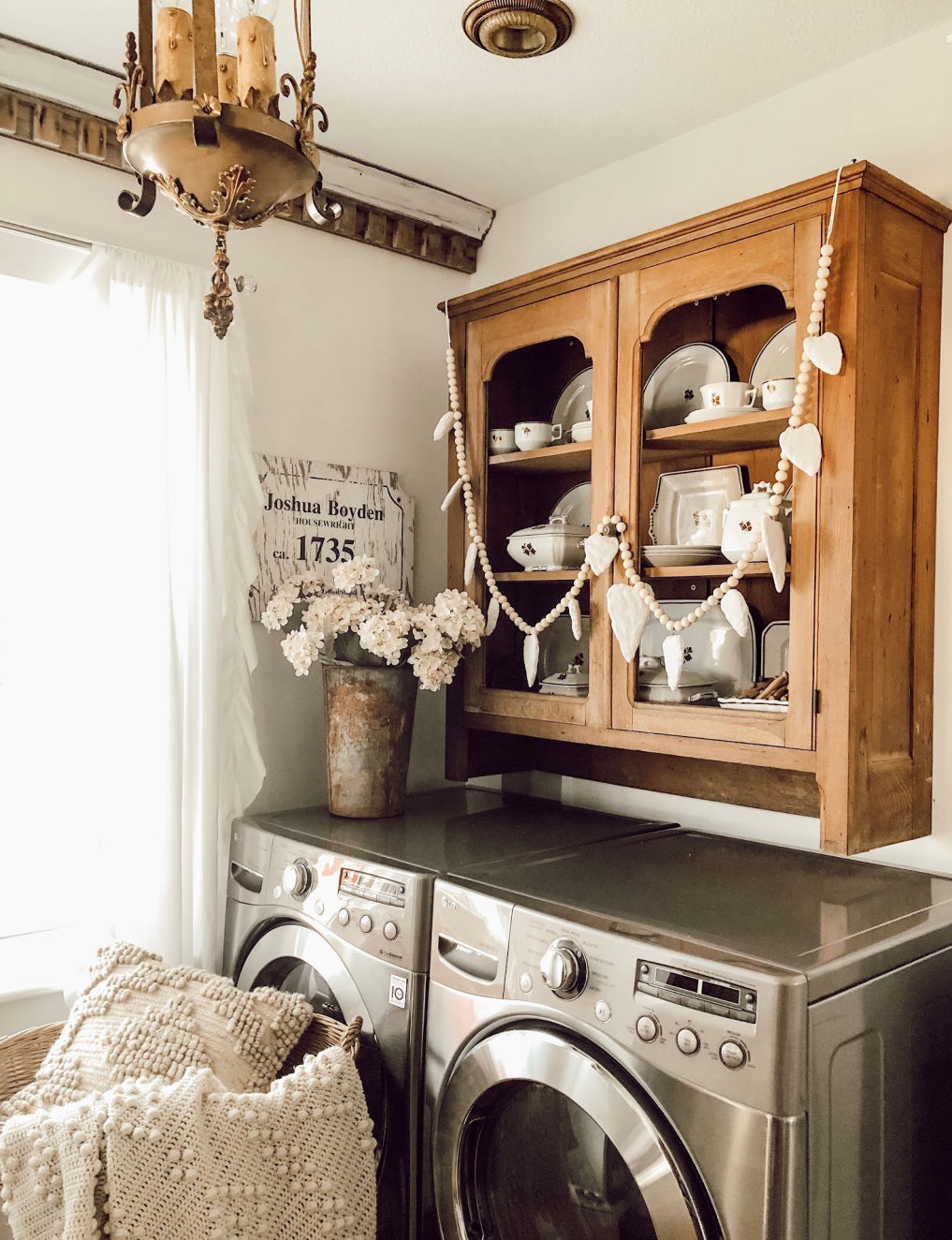 Laundry room with a vintage cabinet over the washer and dryer #farmhousedecor #vintagedecor #farmhouselaundryroom #laundryroom #neutraldecor #cottagestyle