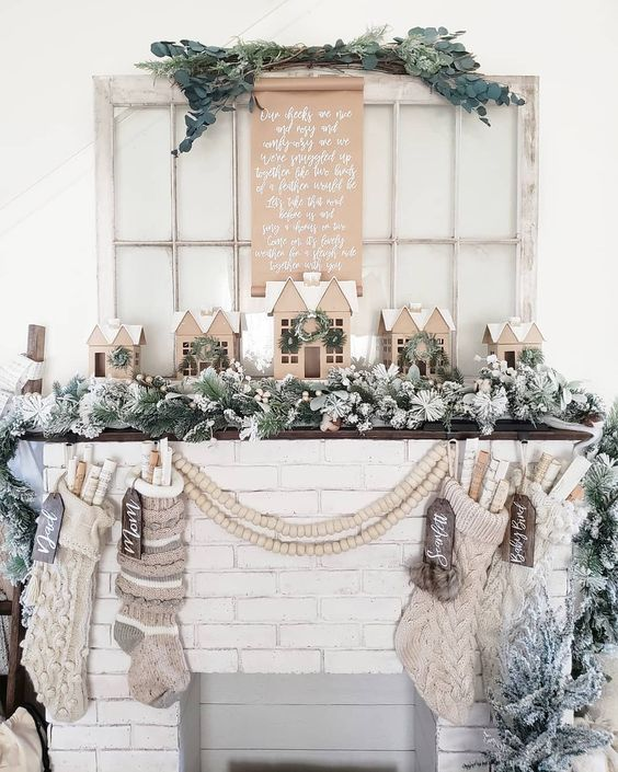 Neutral Christmas mantel with cardboard houses kellyelko.com #christmas #neutralchristmasdecor #christmasmantel #putzhouses #christmasstockings #farmhousechristmas #vintagechristmas #kellyelko #christmasdecorating