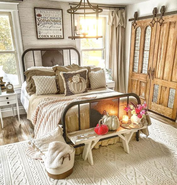 Beautiful farmhouse bedroom with iron bed and old doors turned rolling barn doors kellyelko.com #farmhouse #farmhousedecor #farmhousebedroom #vintagedecor #vintagebedroom #fall #falldecor