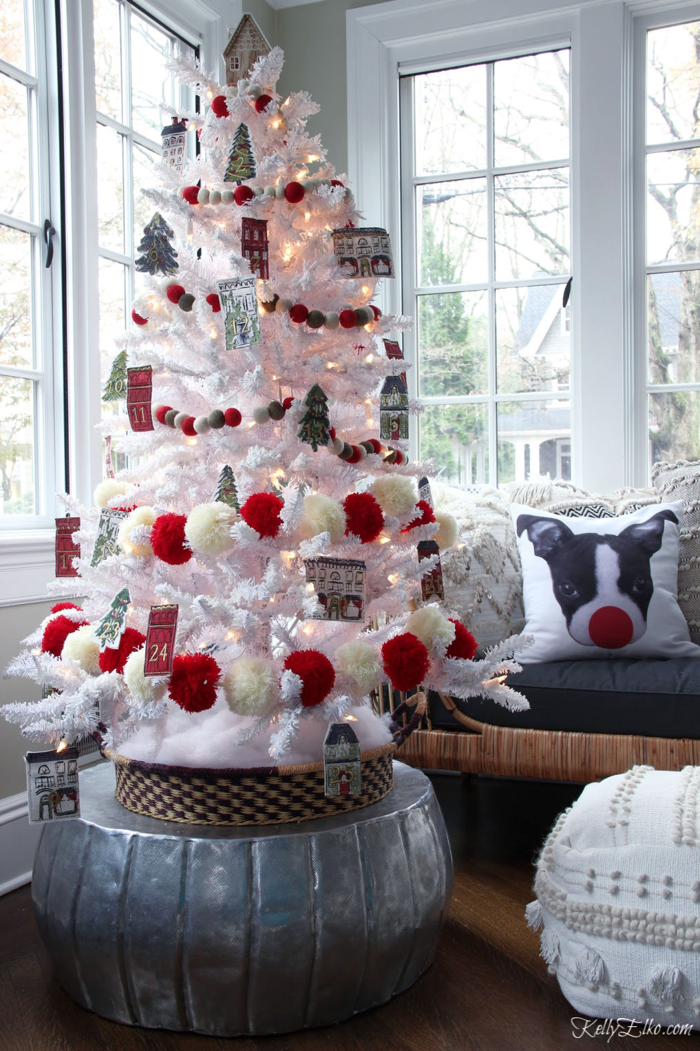 How cute is this Advent calendar Christmas tree to countdown to Christmas kellyelko.com #christmas #christmasdecor #christmastree #diychristmasdecor #adventcalendar #whitechristmastree #flockedchristmastree #redchristmas #pompoms #christmasgarland