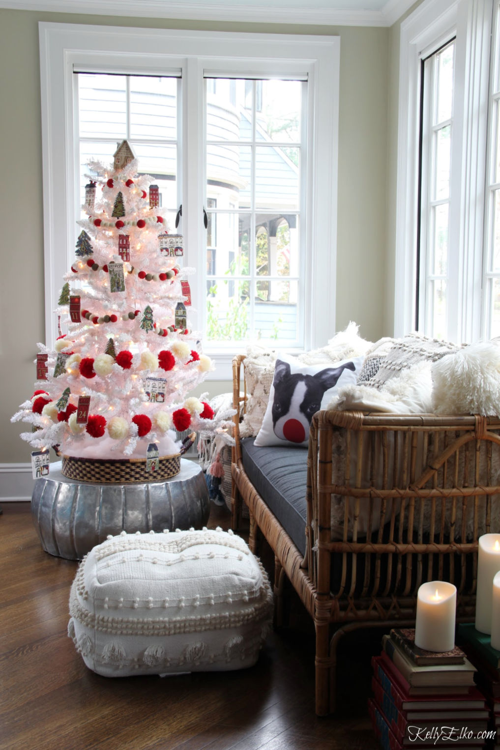 Love this sunroom decked out with a flocked white Christmas tree covered in red and white pom pom garland and Advent countdown ornaments kellyelko.com #sunroom #christmassunroom #rattan #daybed #pouf #christmasdecor #christmastree #christmasornaments #christmasdecorations #diychristmasideas #flockedtree #cozychristmas