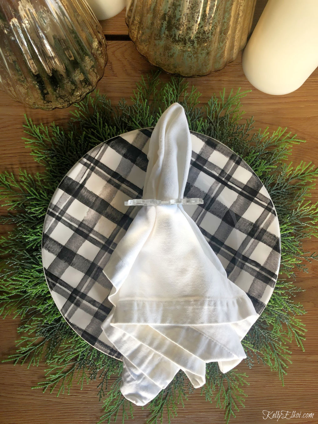 Love this beautiful table setting with black and white plaid plates on a cedar placemat - perfect for Christmas kellyelko.com #christmas #christmastable #christmasdecor #plaid #kellyelko