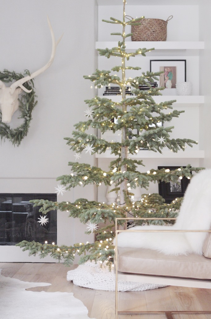 15 Sparse Christmas Trees - love this beautiful Silver Tip tree minimally decorated in lights and stars kellyelko.com #christmas #christmastree #sparsechristmastree #vintagechristmas #christmasdecor #christmasedecorating #christmasdecoratingideas #farmhousechristmas #christmasornaments #neutralchristmas #silvertip #kellyelko
