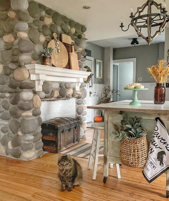 This beautiful stone fireplace separates the kitchen from the breakfast nook in this old farmhouse kellyelko.com #fireplace #farmhouse #farmhousekitchen #farmhousestyle #countrykitchen #cottagekitchen #vintagedecor