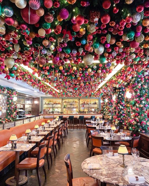 The ceiling of this festive restaurant is covered in Christmas ornaments kellyelko.com #christmas #christmasdecor #christmasdecorations #34mayfair #colorfulchristmas #londonchristmas #londonrestaurants #shinybrites #ornaments