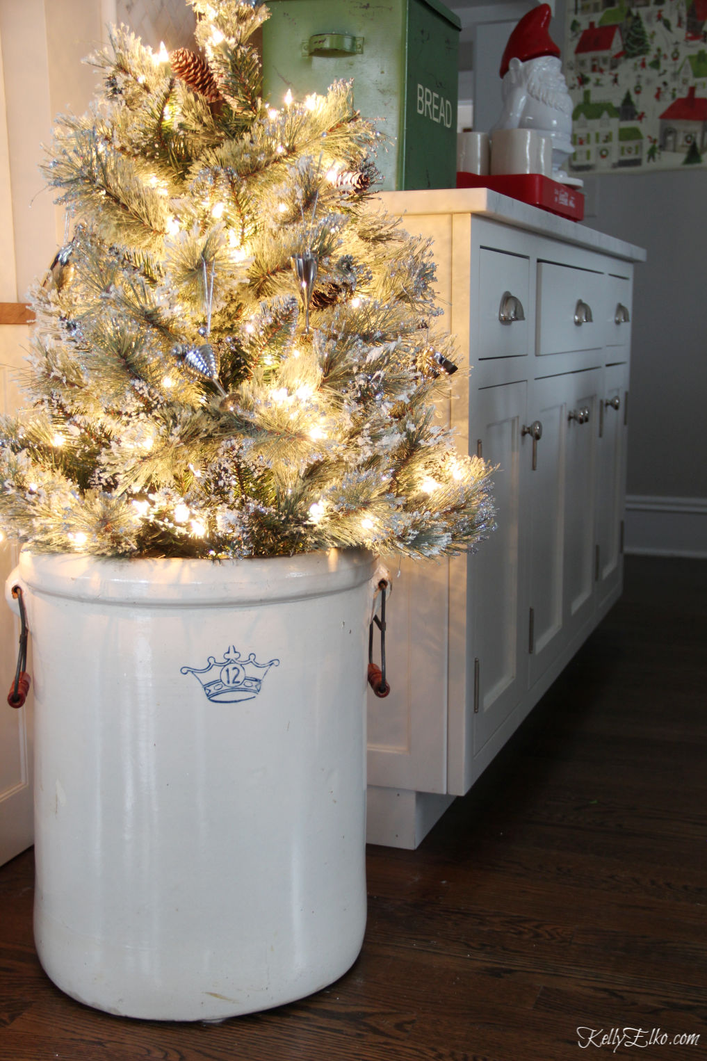 Beautiful vintage modern Christmas home tour - love the antique crock holding a Christmas tree kellyelko.com #christmas #christmasdecor #christmasdecorating #christmashome #christmastour #diychristmas #christmasideas #christmasmantel #christmastree #christmasornaments #vintagechristmas #farmhousechristmas #colorfulchristmas #creativechristmas #kellyelko #crock #vintagecrock #christmaskitchen