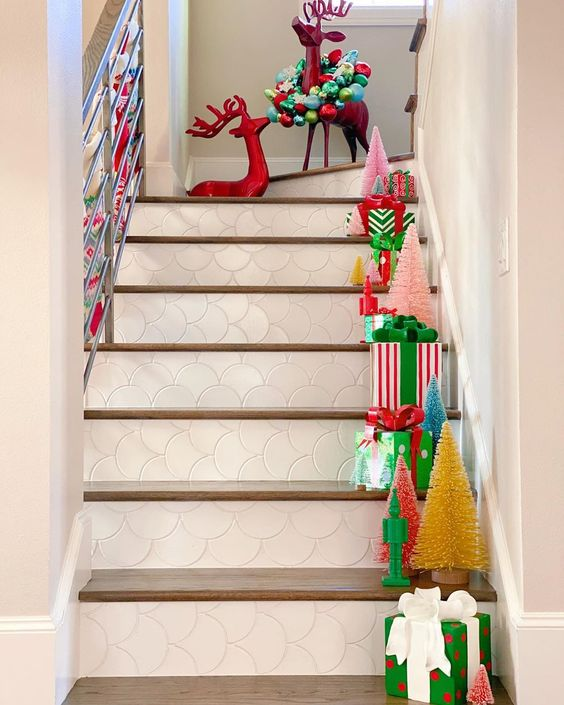 Bottle Brush Tree Ideas - love this staircase filled with colorful trees and gifts #christmasdecor #colorfulchristmas #bottlebrushtrees #christmastrees #christmasstairs