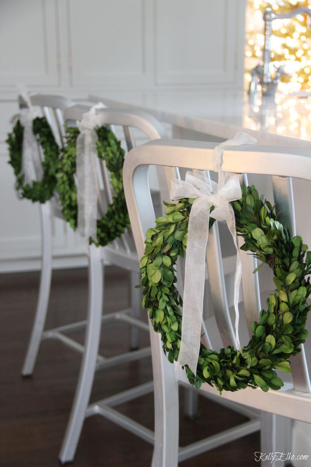 Love this Christmas Home Tour with mini boxwood wreaths on kitchen counter stools kellyelko.com #christmas #christmasdecor #christmasdecorating #christmashome #christmastour #diychristmas #christmasideas #christmasmantel #christmastree #christmasornaments #vintagechristmas #farmhousechristmas #colorfulchristmas #creativechristmas #kellyelko #boxwood #boxwoodwreaths #christmaskitchen
