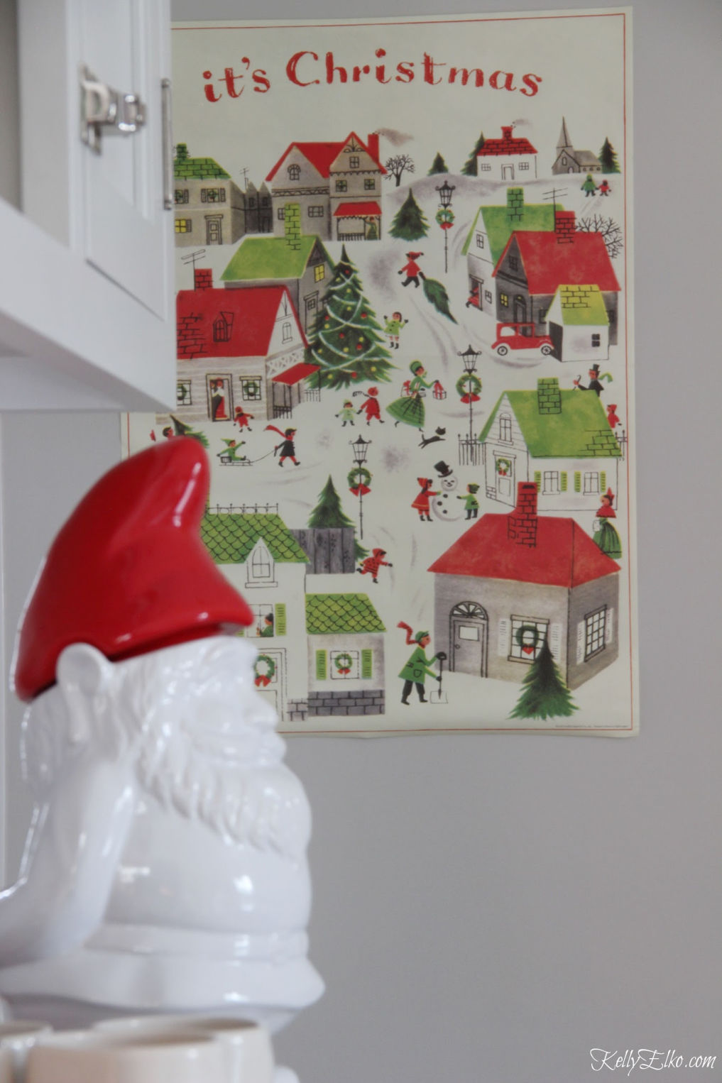 Colorful Christmas Home Tour - love the winter village art in the kitchen kellyelko.com #christmas #christmasdecor #christmasdecorating #christmashome #christmastour #diychristmas #christmasideas #christmasmantel #christmastree #christmasornaments #vintagechristmas #farmhousechristmas #colorfulchristmas #creativechristmas #kellyelko #gnome #christmasvillage #christmasart