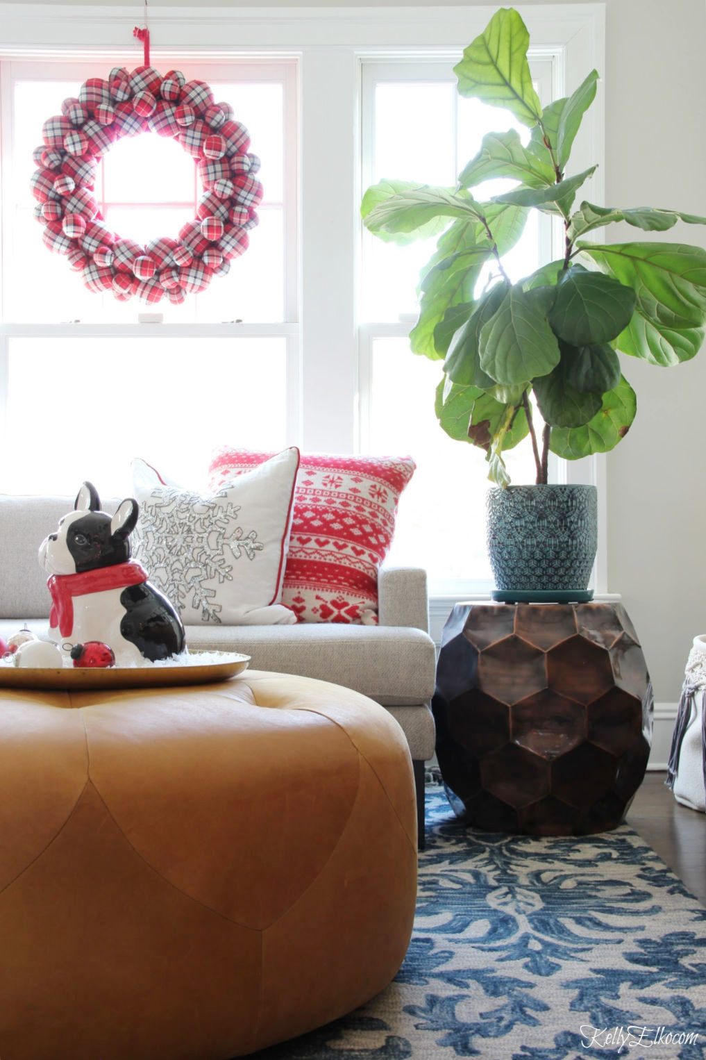 Creative Christmas Home Tour - love this colorful family room with huge red plaid wreath and fiddle leaf fig kellyelko.com #christmas #christmasdecor #christmasdecorating #christmashome #christmastour #diychristmas #christmasideas #christmasmantel #christmastree #christmasornaments #vintagechristmas #farmhousechristmas #colorfulchristmas #creativechristmas #kellyelko #fiddleleaffig #houseplants #plants #plantlady