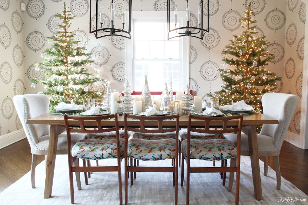 Creative Christmas Home Tour - love this dining room with two Christmas trees in gold and silver kellyelko.com #christmas #christmasdecor #christmasdecorating #christmashome #christmastour #diychristmas #christmasideas #christmasmantel #christmastree #christmasornaments #vintagechristmas #farmhousechristmas #colorfulchristmas #creativechristmas #kellyelko #diningroom #christmasdiningroom #sparsechristmastrees #otomi #farmhousestyle #wallmural