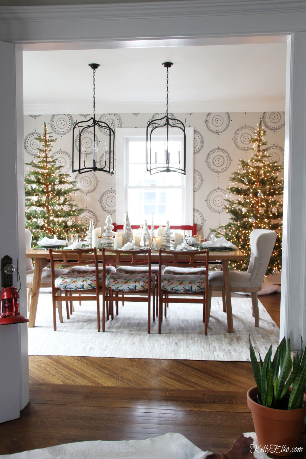 Beautiful Christmas Home Tour - love the pair of sparse Christmas trees in the dining room covered in clear ornaments kellyelko.com #christmas #christmasdecor #christmasdecorating #christmashome #christmastour #diychristmas #christmasideas #christmasmantel #christmastree #christmasornaments #vintagechristmas #farmhousechristmas #colorfulchristmas #creativechristmas #kellyelko #christmasdiningroom #diningroom #lighting #chandeliers