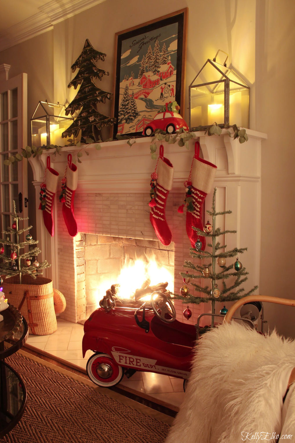 Beautiful Christmas Night Tour and love the roaring fire and festive red pedal car kellyelko.com #christmasdecor #christmasnightstour #christmasmantel #christmaslights #fireplace #roaringfire #vintagechristmas #farmhousechristmas #colorfulchristmas #kellyelko #christmasart #christmassgtockings #feathertrees