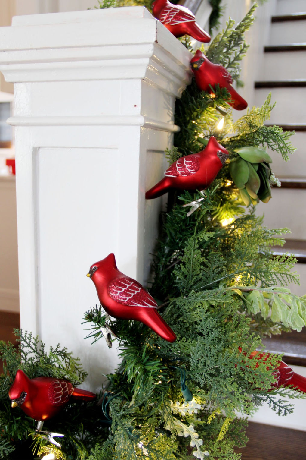 Christmas garland filled with red cardinal ornaments kellyelko.com #christmas #christmasdecor #christmasdecorating #christmashome #christmastour #diychristmas #christmasideas #christmasmantel #christmastree #christmasornaments #vintagechristmas #farmhousechristmas #colorfulchristmas #creativechristmas #kellyelko #cardinals #bannister #christmasgarland #christmasstairs