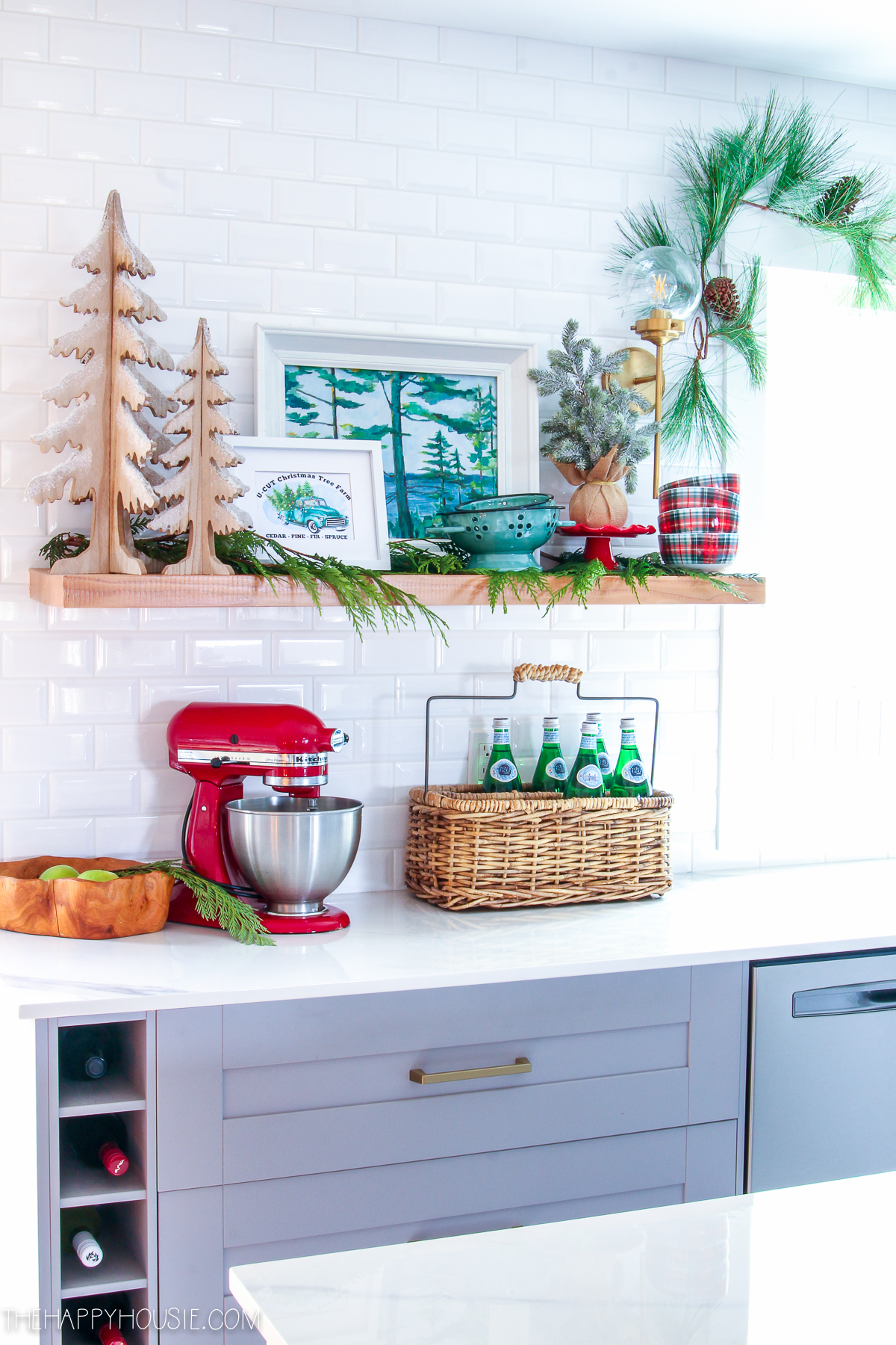 Love this cheery Christmas kitchen #christmasdecor #christmaskitchen #kitchenshelves #subwaytile #kitchenbacksplash #openshelves