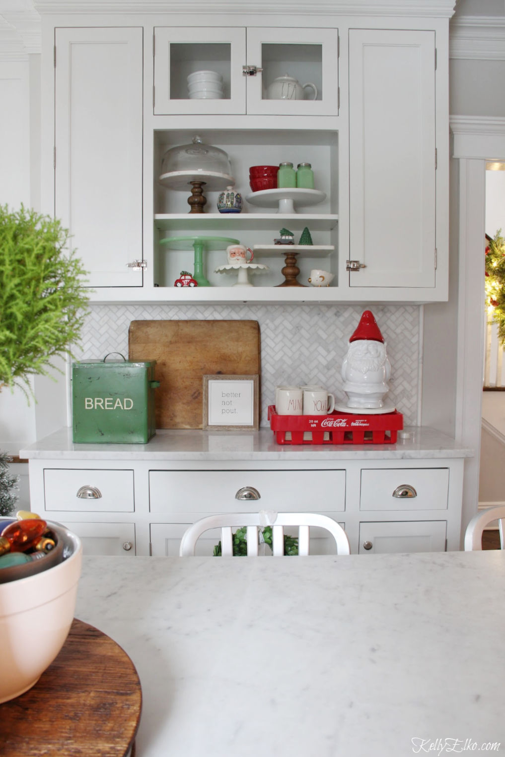 Christmas Home Tour - love the open shelves in this white kitchen decorated in red and green kellyelko.com #christmas #christmasdecor #christmasdecorating #christmashome #christmastour #diychristmas #christmasideas #christmasmantel #christmastree #christmasornaments #vintagechristmas #farmhousechristmas #colorfulchristmas #creativechristmas #kellyelko #christmaskitchen #vintagedecor #breadbox #gnome #openshelves
