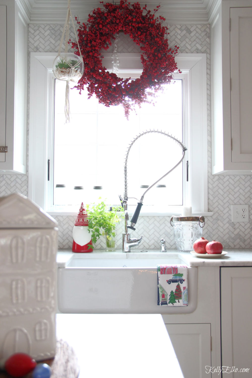 Christmas Home Tour - love the red berry wreath over the kitchen window and the gnome cookie jar in this beautiful white kitchen kellyelko.com #christmas #christmasdecor #christmasdecorating #christmashome #christmastour #diychristmas #christmasideas #christmasmantel #christmastree #christmasornaments #vintagechristmas #farmhousechristmas #colorfulchristmas #creativechristmas #kellyelko #whitekitchen #marbletile #kitchenwindow #berrywreath #christmaswreath #christmaskitchen