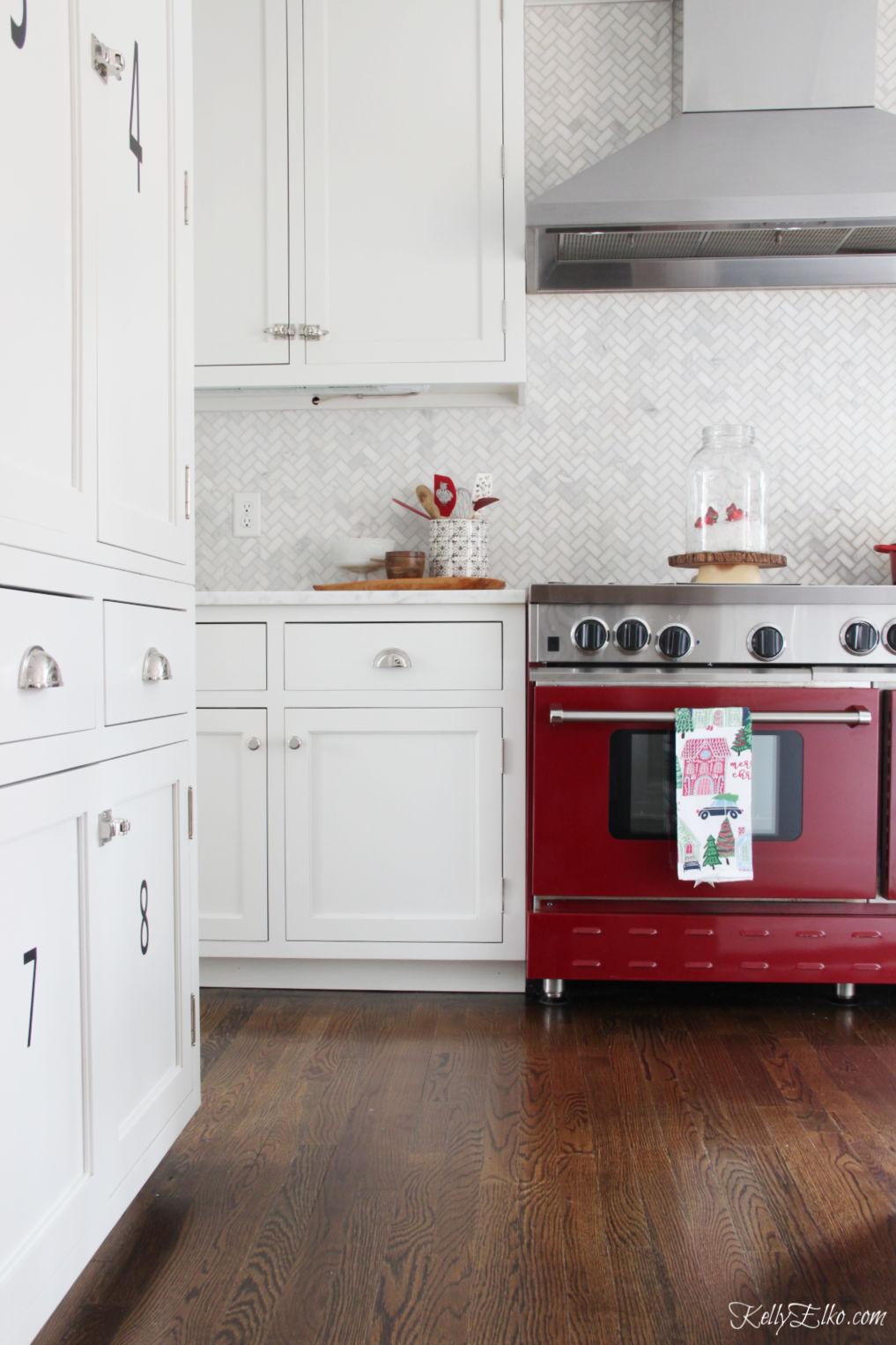 Beautiful white kitchen with red stove, carrara herringbone tile and white cabinets kellyelko.com #christmas #christmasdecor #christmasdecorating #christmashome #christmastour #diychristmas #christmasideas #christmasmantel #christmastree #christmasornaments #vintagechristmas #farmhousechristmas #colorfulchristmas #creativechristmas #kellyelko #redstove #stove #backsplash #whitekitchen