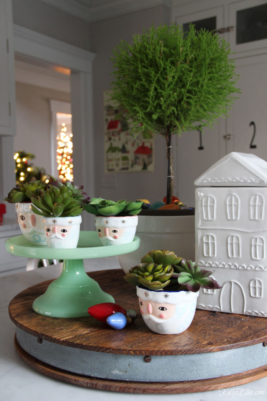 Christmas in the Kitchen - love the Santa measuring cups and house cookie jar kellyelko.com #christmas #christmaskitchen #christmasdecor #christmasdecorations #topiary #vintagechristmas #kellyelko