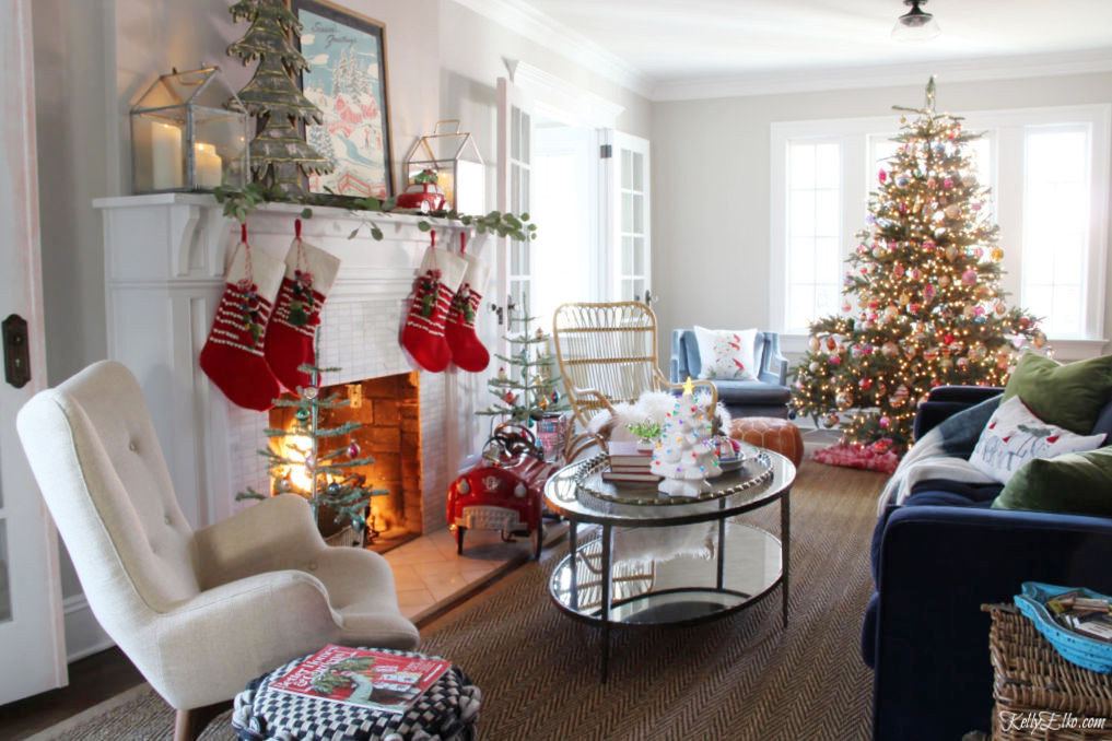 Beautiful Christmas Home Tour - love this whimsical mantel with colorful pom pom stockings and tree covered in vintage ornaments kellyelko.com #christmas #christmasdecor #christmasdecorating #christmashome #christmastour #diychristmas #christmasideas #christmasmantel #christmastree #christmasornaments #vintagechristmas #farmhousechristmas #colorfulchristmas #creativechristmas #kellyelko #christmaslivingroom #shinybrites #vintageornaments