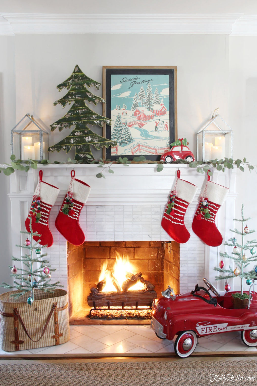 Christmas Home Tour filled with creative decorating ideas like this mantel with retro art kellyelko.com #christmas #christmastour #christmashometour #christmasmantel #vintagechristmas #farmhousechristmas #colorfulchristmas #cozychristmas #retrochristmas #christmasstockings #fireplace #vintagedecor